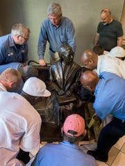In this Nov. 19, 2015 photo, workmen help sculptor