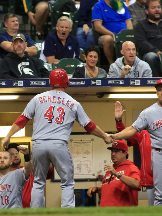 Cincinnati Reds' Scott Schebler, center, is congratulated after scoring against the Milwaukee Brewers during the ninth inning of a baseball game Saturday, Sept. 24, 2016, in Milwaukee. (AP Photo/Darren Hauck)2