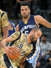 San Antonio Spurs guard Tony Parker (9) drives around Memphis Grizzlies guard Andrew Harrison during the first half of an NBA basketball game, Thursday, March 23, 2017, in San Antonio.