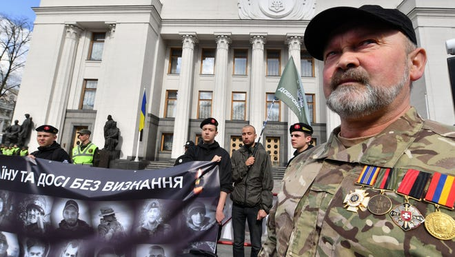 "Fighters of the Ukrainian volunteer battalions, warring on Donbass region with pro-Russian separatists, rally in front of the parliament's building in Kiev on April 19, as they demand the lawmakers to approve a bill giving them the social status ""war participants."""
