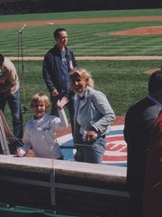 Noah Jack Cummins waves next to his mom, Barbara, after singing the national anthem at Wrigley Field before a Cubs game.