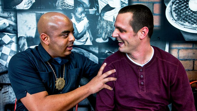 """The Rev. Jarrett Maupin (left) speaks to ASU police Officer Stewart Ferrin during a """"lemonade summit"""" at Lolo's Chicken and Waffles in Phoenix on Tuesday, Jan. 27, 2015."""