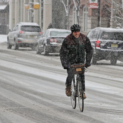 A man pedals on a bicycle as a steady snow falls in