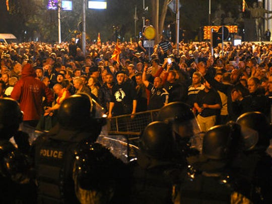 Police cordon blocks protesters to enter into the parliament building in Skopje, Macedonia, Thursday, April 27, 2017. Chaos swept into Macedonia's parliament Thursday as demonstrators stormed the building and attacked lawmakers to protest the election of a new speaker despite a months-old deadlock in efforts to form a new government.