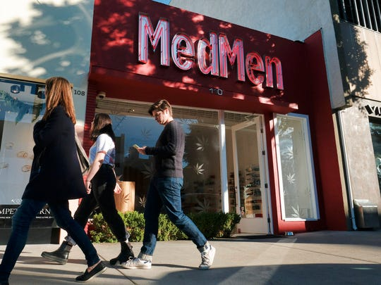 In this Thursday, Dec. 21, 2017, file photo pedestrians walk past one of the MedMen marijuana dispensaries in Los Angeles.