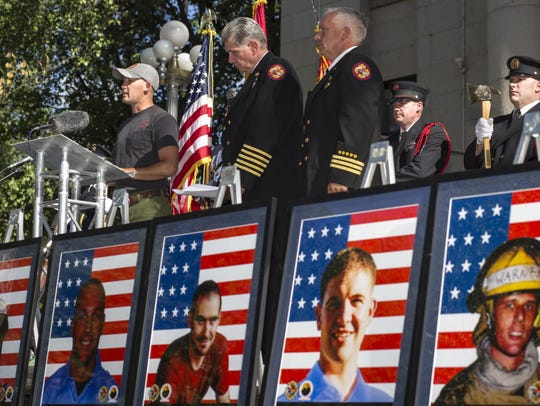 Firefighter Pat McCarty (left) reads the names of the