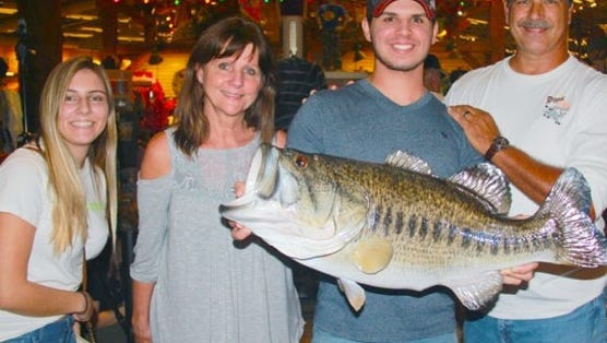Dominic Montalto holds a replica taxidermist mount of the giant bass of 16 pounds, 12 ounces that he caught and released on his way to first place in the 2016-17 TrophyCatch competition. Members of Montalto's family joined him at the recent TrophyCatch Hall of Fame awards presentations at Bass Pro Shops in Orlando.