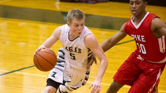 Zionsville senior Braden Hall (5) races the ball toward the basket around the defense of Pike sophomore Justin Roberts (10), Jan. 27, 2015. Zionsville defeated Pike 61-58.