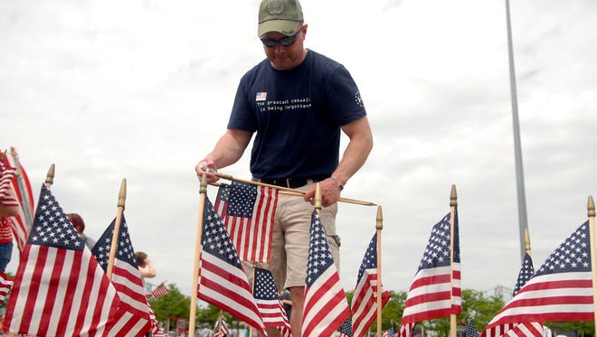 """Army Veteran Jason Holman places flags in the shape of """"USA"""" at the Flag4Vets Memorial Day service on the Great Lawn at Waterfront Park.  Fifteen thousand flags were placed in memory of fallen soldiers."""