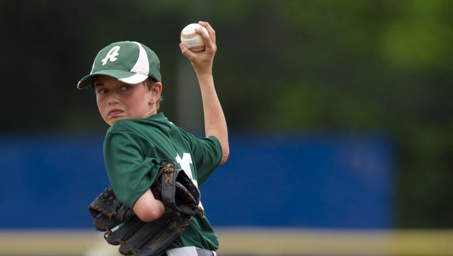 12-year-old Aidan Duncan delivers a pitch to the plate as he takes a turn on the mound.