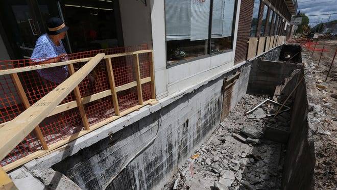 Betty Stoch of Marshfield looks down at two large rooms that were uncovered as the road is rebuilt at the corner of 4th and Central in Marshfield, Tuesday, August 4, 2015. The rooms served several functions including being a delivery and storage area for what was once Weber's grocery store. The building is currently owned by Shelby Weister and is the home of Janet's Yarns and Crafts.
