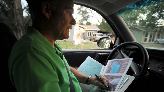 Dale Wood, the City of Fort Collins compliance inspector, takes down a few notes on a house he is investigating as he goes through his rounds enforcing the city's three-unrelated ordinance Aug. 30, 2012.