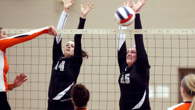 Siegel's Kayla Mize (14) and Katelyn Lester (25) jump up to try and block a ball hit by Blackman's Tristyn Lozano (10), left, as Blackman players Hailey Ivy (16), middle, and Delaney King (18), right, watch at the net during the Region 4-AAA volleyball Championship, on Tuesday, Oct. 13, 2015, at Siegel.