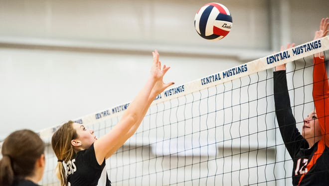 Badger Jensen Knaub hits the ball as Miner Danielle Betts leaps to block during the District 7C volleyball tournament at Great Falls Central Catholic High School on Thursday.
