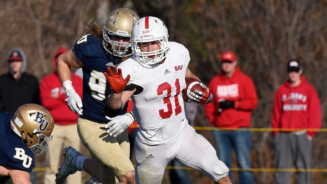 St. John's University's Sam Sura pushed away Bethel defenders as he gains yards on a run in the first half Saturday at Bethel.