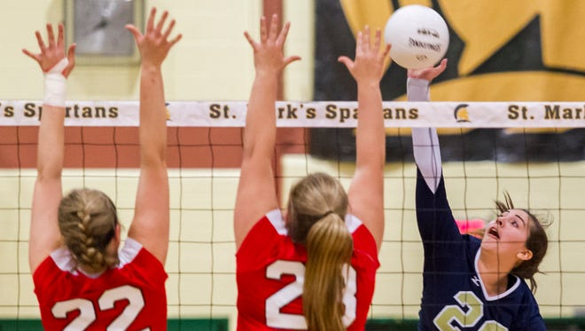 Delaware Military Academy's Jacqualine Shields (No. 20) sends the ball into the block attempt of Ursuline's Nicole Raiford (No. 22) and Sophia Simoes (No. 23) in the third game of DMA's 3-0 win over Ursuline in the DIAA volleyball semi-finals at St. Mark's High School on Thursday night.