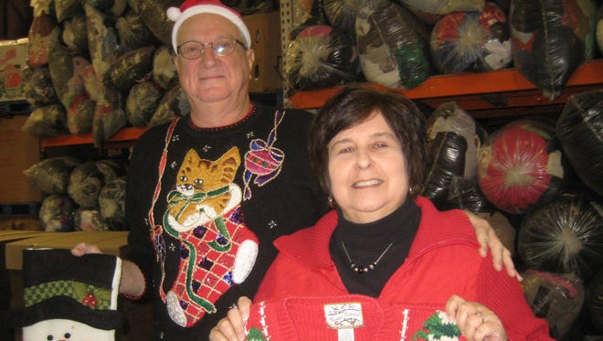 Patrick and Joan Sheehy show some of the holiday-themed sweaters, sweatshirts and accessories Master Provisions will offer Saturday at two shopping locations. Shop at Master Provisions' Borland Family Distribution Center in Florence or at Fairfield Christian Church, 745 Symmes Road, Fairfield.