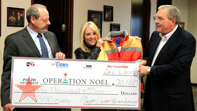 El Paso Mayor Oscar Leeser and his wife, Lisa, donate $20,000 to the 2015 Operation Noel coat drive as Dee Margo, right, accepts their donation. The mayor saved his salary for the past six months and donated it to the yearly campaign. With the donation, about 1,480 coats will be purchased to help bring the total number of coats to be given out this year to 20,000, up from last year's 19,000.