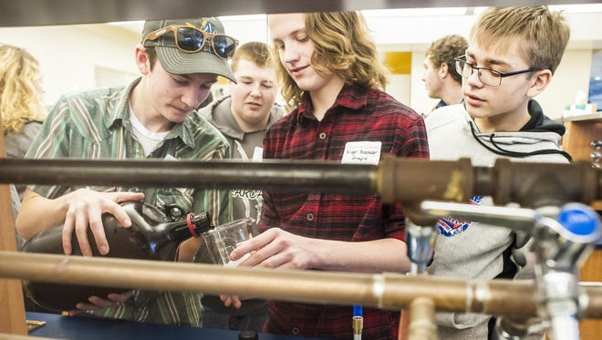 Left to right, Kenneth Vincent, Bridger Boedcker and Connor Simpson pour a chemical into a cup to watch a piece of Styrofoam dissolve as part of a chemistry demonstration during University of Great Falls' Science Days in the DiRocco-Peressini Science Building on Wednesday.