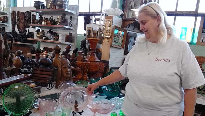 Myerstown Indoor Flea Market manager Brenda Oudinot looks at glassware she has for sale. The flea market is inside the former Publix Shirt Co. building on East Main Avenue in Myerstown.