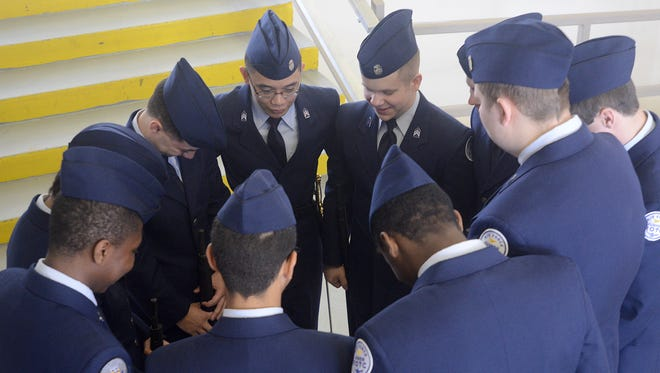 Members of the North Side High School Air Force JROTC huddle up before competing in the armed regulation drill at the Oman Arena on Saturday.