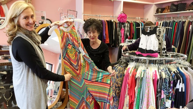 Kate Surmeier gets some help from Peggy Armstrong at Second Time Around during Ms. Cheap's consignment tour.