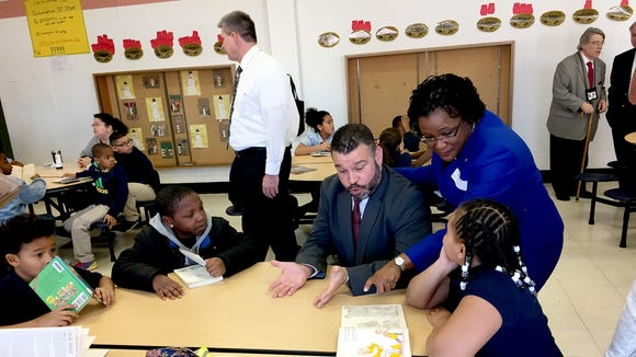 Education Secretary Pedro Rivera and York Mayor Kim Bracey talk with students in the cafeteria at Goode K-8 School, where students read each day during lunch.