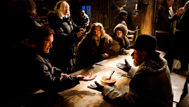 """Quentin Tarantino (far left) directs a scene with Kurt Russell (seated), Jennifer Jason Leigh and Tim Roth on the set of """"The Hateful Eight."""""""