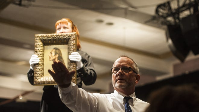 An auctioneer gestures to a bidder during First Strike Auction at the Mansfield Convention Center on Friday.
