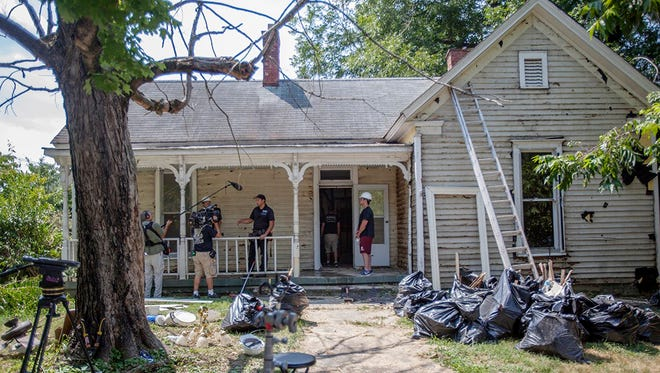 TV crews interview house flipper Troy Dean Shafer on the porch of a dilapidated home in Springfield, Tenn.