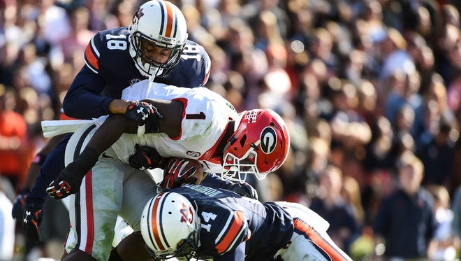 Stephen Roberts (14) and Carlton Davis (18) make a tackle during a game against Georgia in Auburn, Ala. on Saturday, Nov. 14, 2015. Roberts was arrested on Wednesday night and charged with attempting to elude an officer and carrying a firearm without a license.