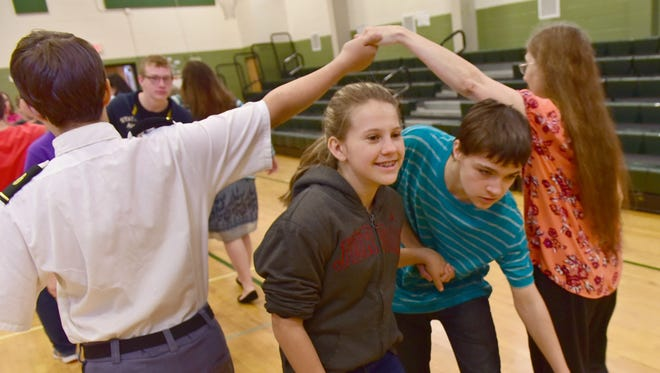 Jordan Sheaffer, left, and Jacob Patterson pass through an arch during a dance lesson. James Buchanan Middle School eighth-graders hosts the Grand Ball at school Friday, May 13, 2016.  Students were performing dances from the American Revolution and the Civil War, taught by dancers Jeff Savage and Nancy Walker of Danza Antiqua.