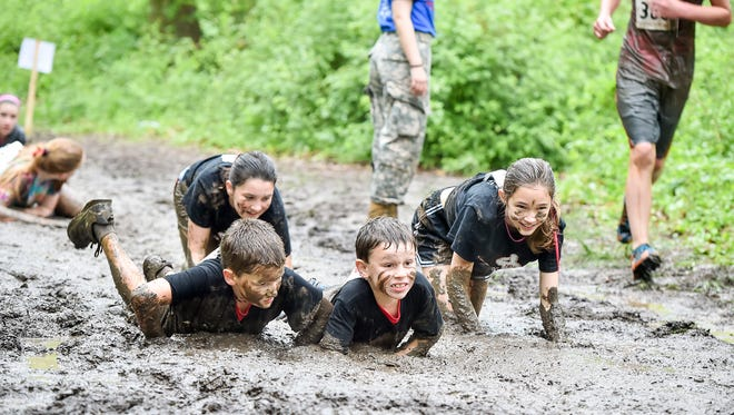 One obstacle course requires runners to crawl through thick mud during the Fourth Annual Boro Indian Dash on Saturday, May 14, 2016 at Renfrew Park in Waynesboro, Pa. The race will benefit Franklin County Save a Vet Save a Pet.