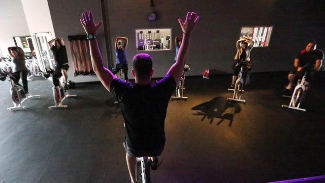 Brian Guzman leads a spinning group in stretching at the start of a class at Rock Solid Fitness, 1477 Lomaland, Suite A-9. Spinning is still popular across the United States.