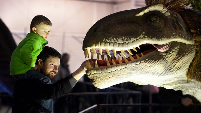 Stewart Ellis watches as his dad, Adam, touches the teeth of one of the many dinosaurs on display at Jurassic Quest during an exhibit in Tennessee. Jurassic Quest is in Montgomery for this weekend. .