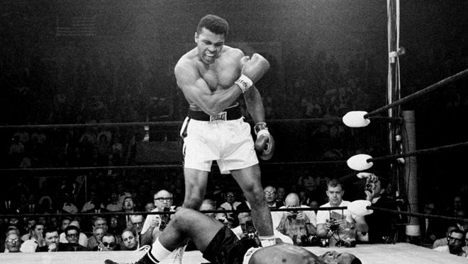 In this 1965 file photo, heavyweight champion Muhammad Ali, then known as Cassius Clay, stands over Sonny Liston after dropping him with a short hard right to the jaw in Lewiston, Maine.