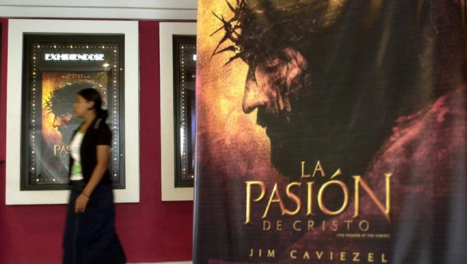 """A woman walks in a movie theater showing a sneak preview of """"The Passion of The Christ"""" in Managua, Nicaragua, Wednesday, March 17, 2004."""