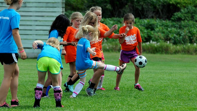 A teammate on the blue team kicks the ball high during a Sartell Community Ed youth soccer league game at Sartell High School soccer field on Monday in Sartell.