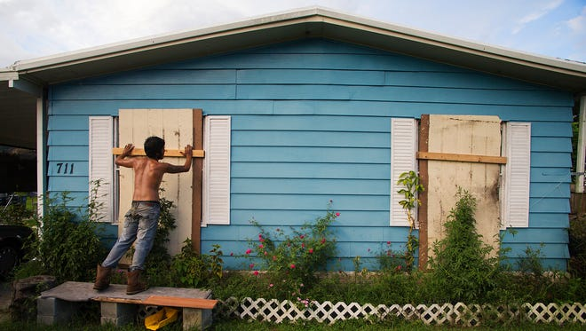 Edwin Almaras prepares his family's mobile home Wednesday for Hurricane Matthew in Clewiston, Florida.
