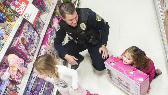 Det. Scott Bambenek picks out toys with Layla, left, and Remington McDermott, right, during the Shop With a Cop event at Target last year.