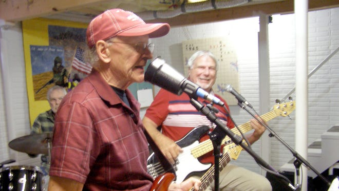 Chuck Roman, left, plays lead guitar; Ed Barton, right, is on bass; Jerry Garten, rear, plays drums.