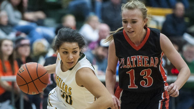 C.M. Russell's Akasia Denton rushes past Flathead's Averie Olson during the game at CMR on Friday.