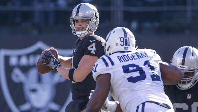 Oakland Raiders quarterback Derek Carr (4) drops to pass against the Indianapolis Colts at Oakland Alameda Coliseum in Oakland, Calif., on Saturday, Dec. 24, 2016.