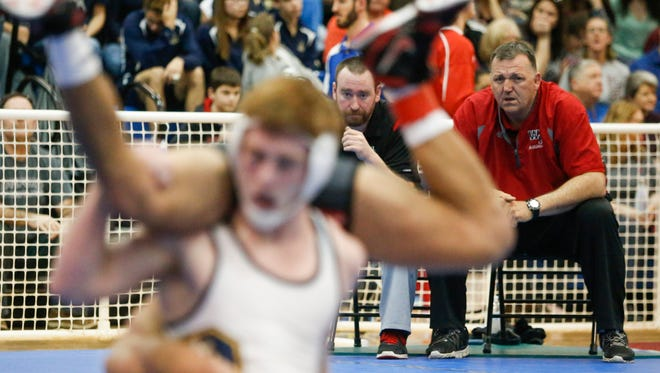 William Penn head coach Marvin Dooley (right) watches one of his wrestlers with assistant Jason Land during the quarterfinal round of the individual state DIAA tournament at Dover High School Friday.