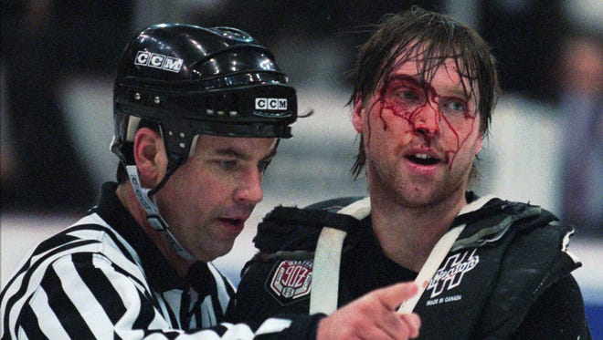 Linesman Dan Schachte leads a bleeding Colorado Avalanche goaltender Patrick Roy to his bench after a brawl with Detroit Red Wings goaltender Mike Vernon on Wednesday, March 26, 1997.