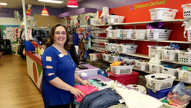 Children's Orchard owner Angie Geldert takes in clothing at her Murfreesboro children's resale store.