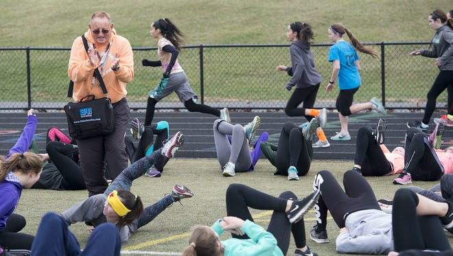 York Suburban head track coach Dave Wickenheiser leads a stretching exercise earlier this year. Wickenheiser retired at the end of the school year from teaching and coaching.