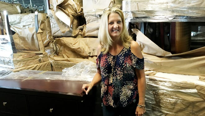 Cherilyn Pollard shows off one of the Opryland Hotel dressers that will be included in the  Suite Upgrades three day warehouse sale in Lebanon.