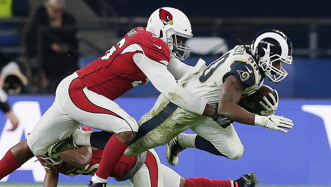 Los Angeles Rams running back Todd Gurley (30) is tackled by Arizona Cardinals inside linebacker Karlos Dansby (56) during the second half of an NFL football game against Arizona Cardinals at Twickenham Stadium in London, Sunday Oct. 22, 2017.