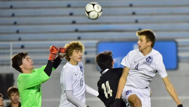 Hempfield goalie Brady Ross makes a save in front of Chambersburg's Aaron Maynard (15) and Luke Myers. Chambersburg played Hempfield in D3 Class 4A semifinal boys soccer, October 31, 2017 in Hershey. Hempfield won 2-0.
